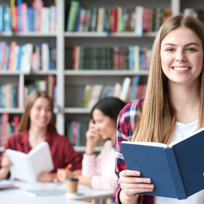 Young student with book in library, space for text. Banner design