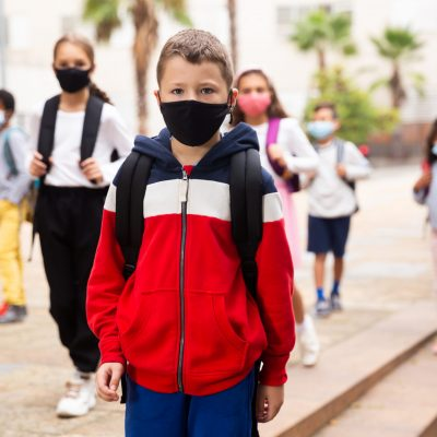 Confident tweenager in protective mask walking with other schoolchildren to school campus after lessons on spring day. Concept of necessary precautions in COVID pandemic